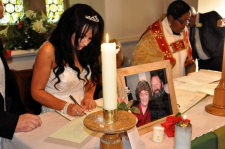 Lisa signing the register with a photograph of her mum and dad in the altar.